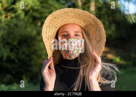Schöne junge Frau trägt eine stilvolle modische Coronavirus Gesichtsmaske während Covid-19 Pandemie Lockdown - Stockfoto