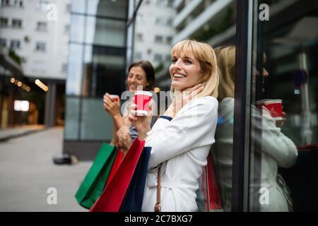 Fröhliche junge Frau, die nach dem Einkaufen in der Stadt Kaffee trinkt und mit Taschen spazieren geht.