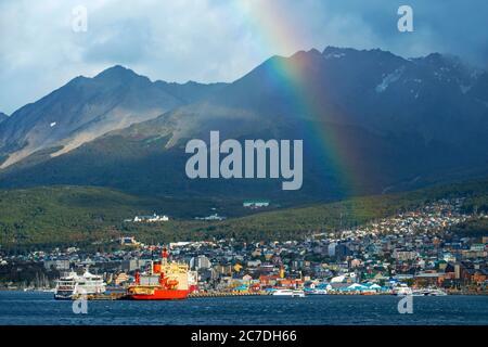 Regenbogen in Ushuaia Hafen Küste und Berge und die Stadt im Hintergrund Ushuaia, Feuerland, Argentinien. - Stockfoto