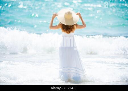 Strandurlaub. Heiße schöne Frau in Sonnenhut und Bikini stehend mit ihren Armen zu ihrem Kopf angehoben genießen Blick auf Strand Ozean. Reisen Stockfoto