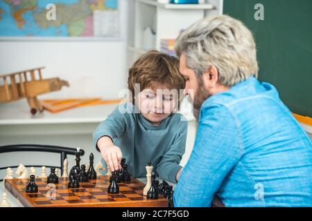 Generationen Männer. Niedlicher kleiner Junge, der mit Eltern Schach spielt. Netter kleiner Junge, der konzentriert am Tisch sitzt und mit seinem Vater Schach spielt