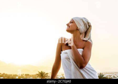 Vorderansicht einer jungen Frau, die nach dem Duschen auf einem Balkon in ein weißes Handtuch gehüllt steht. Mädchen genießt einen Blick auf die Berge und den Sonnenuntergang. Reinigen Sie A - Stockfoto