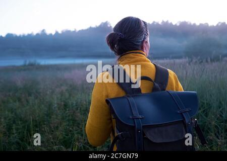 Kaukasische Frau, die am Morgen durch die Wiese geht - Stockfoto