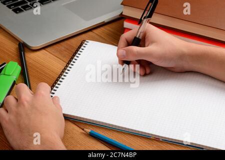 Kursteilnehmer, der mit einem Stift Notizen in einem Notizblock macht - Stockfoto