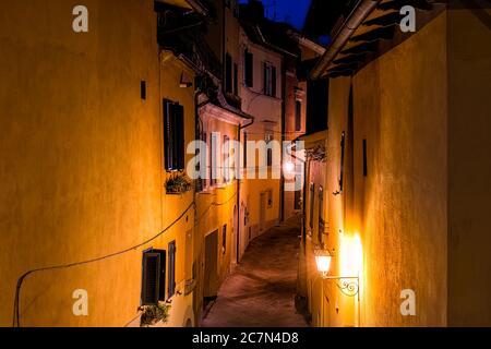 Oben Blick auf Chiusi, Italien Straße schmale Hintergasse in kleinen historischen Dorf in der Toskana in der Nacht mit bunten Gebäuden rosa und o