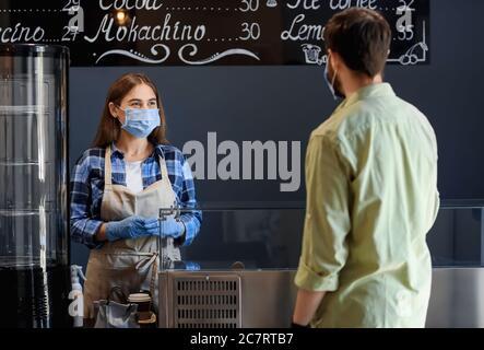 Weibliche Barista mit Gast in einem modernen Café. Konzept der Epidemie - Stockfoto