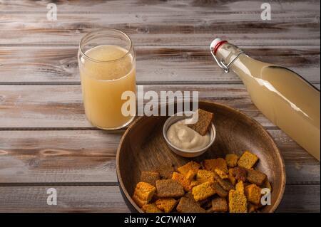 Draufsicht hausgemachte tradishional russischen Licht Roggen Kvass in der Flasche mit Glas Tasse und Cracker auf Holzhintergrund. Wunderbar gesundes Erfrischungsgetränk für den Sommer - Stockfoto