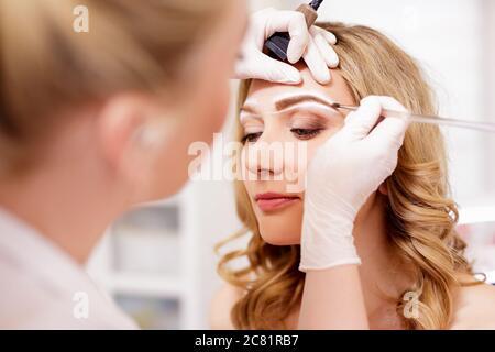 Make-up und Beauty-Konzept - Nahaufnahme von Make-up Künstler Malerei Augenbrauen im Beauty-Studio - Stockfoto