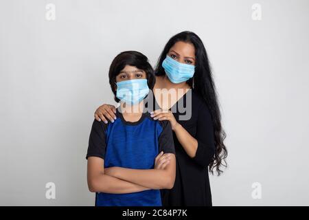Indische Mutter und Sohn tragen Covid Schutzmaske, Frau und kleiner Junge stehen zusammen mit Gesichtsmaske - Stockfoto