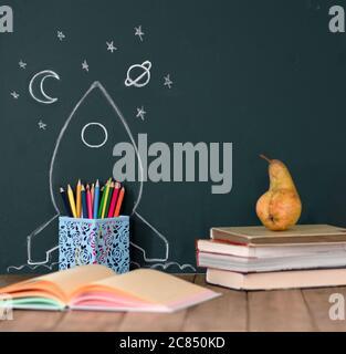 Back to School Konzept mit handgezeichneter Rakete und Sternen auf Blackboard. Buntstifte und Bücher auf einem Holztisch. Stockfoto