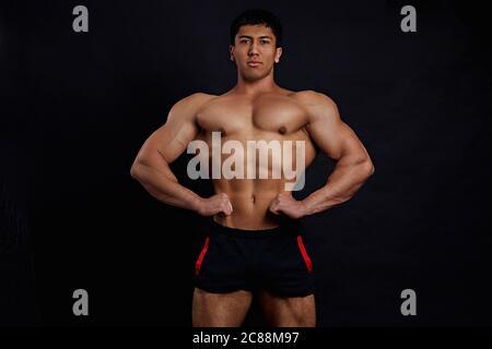 Professionelle Bodybuilder Entwicklung von Muskulatur. Nahaufnahme Foto. Bodybuilder nimmt an einem Wettbewerb. Studio-Aufnahme - Stockfoto