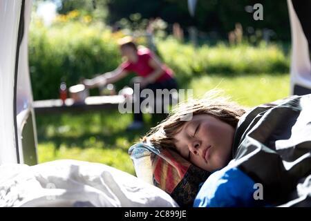 Porträt eines Jungen schlafen in einem Van mit offenen Türen, Mutter bereitet Frühstück draußen auf einer Veranda in der Natur