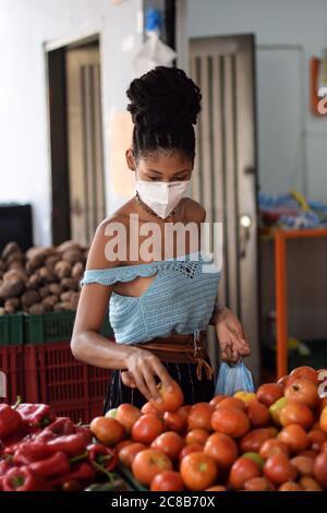 Junge schwarze lateinische Frau Kauf Gemüse in Gesichtsmaske - Stockfoto