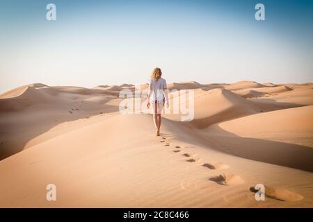 Blonde weibliche kaukasische Reisende verlassen Fußspuren in Sanddünen, wenn in Dessert in Oman zu Fuß