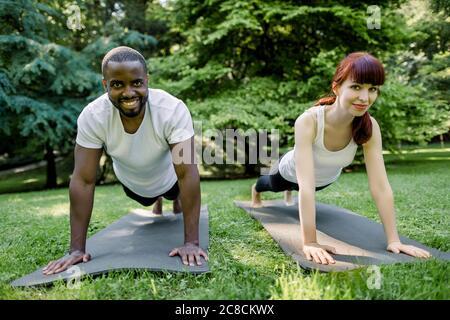 Charmante junge rothaarige kaukasische Mädchen und gutaussehende muskulösen afrikanischen Mann, trägt in weißen T-Shirts und schwarzen Hosen tun eine Übung Plank auf Matten - Stockfoto