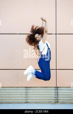 Sorglose junge Frau mit afro Haar springen gegen Wand in Stadt - Stockfoto