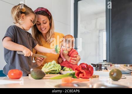 Mutter hält Baby Mädchen während Führung Tochter in Gemüse schneiden Auf Kücheninsel Stockfoto