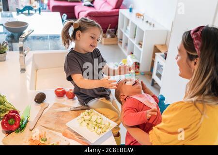Glückliche Mutter und Tochter spielen mit Baby Mädchen in der Küche Zu Hause Stockfoto