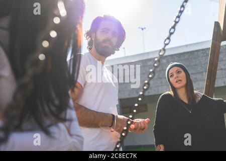 Junger Mann im Gespräch mit Freundinnen, während sie gegen klar stehen Himmel an sonnigen Tag