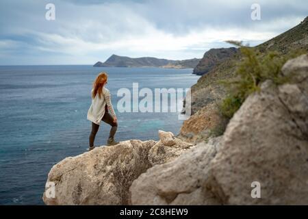Rückansicht einer Frau, die auf dem Meer gegen den Himmel blickt, während sie auf dem Felsen steht - Stockfoto