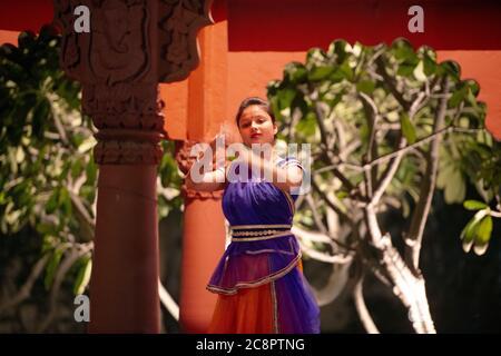 Eine junge Dame führt einen traditionellen Tanz in einem bunten Kostüm in Indien. - Stockfoto