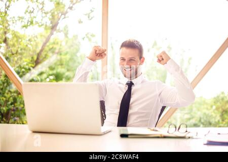 Fröhlicher Geschäftsmann feiert mit erhobenem Arm in der Luft, während er an einem Schreibtisch in seinem Heimbüro sitzt und an einem Laptop arbeitet. Heimbüro. - Stockfoto