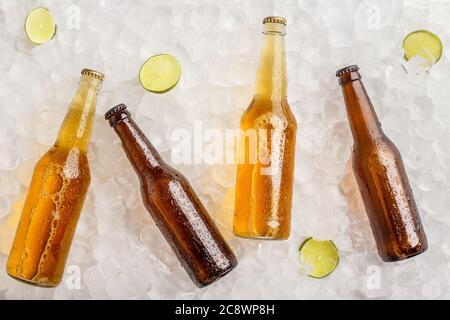 Verschiedene Biere gekühlt für Party. Kalte Glasflaschen mit Bier in Eis mit Limette