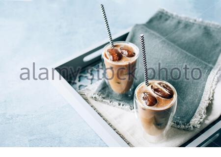 Zwei Gläser Cappuccino-Eiskaffee mit Eis auf grauen Servietten auf Holztablett. Kaltes Gebräu mit Milch Sommer erfrischenden Getränk. Für Text platzieren. - Stockfoto
