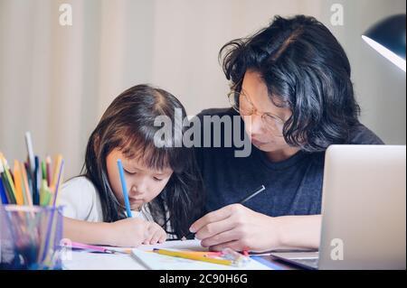 Home Schule Konzept, Vater lehren Tochter asiatische Kinder tun Schule Hausaufgaben und seine Verwendung Laptop machen Überstunden in Arbeitstisch in zu Hause in der Nacht Zeit - Stockfoto