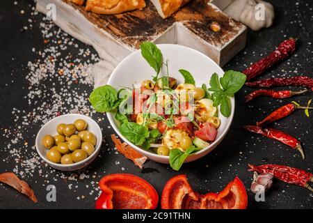 Nahaufnahme köstlicher Salat mit gebratenem Halloumi-Käse, Tomaten, Paprika, Oliven und Rucola und Brot mit Käse. Mediterrane Gerichte