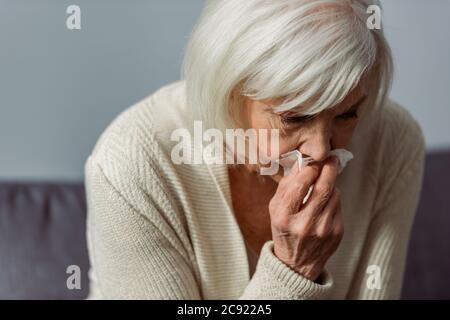 Depressive ältere Frau weint, während sie Papierserviette hält