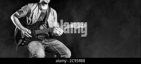 Jazz-Gitarrist auf E-Gitarre. Männlicher Gitarrist spielt Blues und Jazz. Schwarzweiß-Panoramabild. - Stockfoto