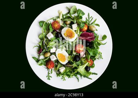 Gesunder grüner Salat mit gekochtem Ei, Feta, Oliven, Kirschtomaten auf weißem Teller auf schwarzem Hintergrund. Flach liegend, Draufsicht