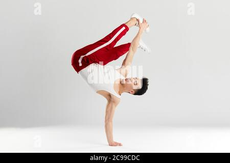 Junge koreanische männliche Tänzerin, die grundlegende Einfrierungen von Downrock Break ausführt, zeigt die Tanzbewegungen des zeitgenössischen Tanzes in sportlichen roten Trainingshosen für den Sport Stockfoto