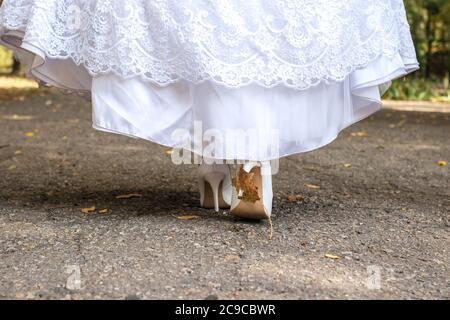 Schöne Braut Schuhe Blick aus unter dem Hochzeitskleid - Stockfoto
