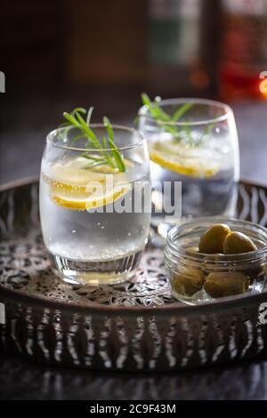 Alkoholische Getränke (Gin Tonic Cocktails) mit Zitrone Rosmarin und Eis auf einem brünierten Metall Getränke Tablett. Hochformat