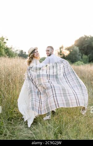 Junge schwangere Paar auf dem Feld während Sommer Sonnenuntergang. Hübscher Junge und sein hübsches schwangeres Mädchen umarmen sich gegenseitig, bedeckt mit karierter Decke - Stockfoto
