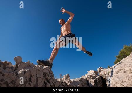 Aktiv schnell laufen Berg verschwitzten Körper muskulösen Läufer Springen über die Spalte Klippe während des morgendlichen Joggens. Sportliche Menschen Aktivitäten Weitwinkel - Stockfoto