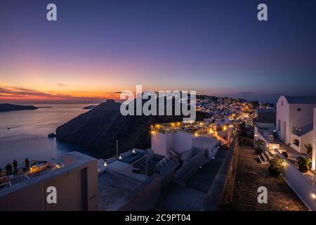 Sonnenuntergang auf dem berühmten griechischen Ferienort Fira, Griechenland, Europa. Hintergrund des Reisekonzepts. Romantische Insel Santorini bei Sonnenuntergang, tolle Aussicht, Lichter - Stockfoto