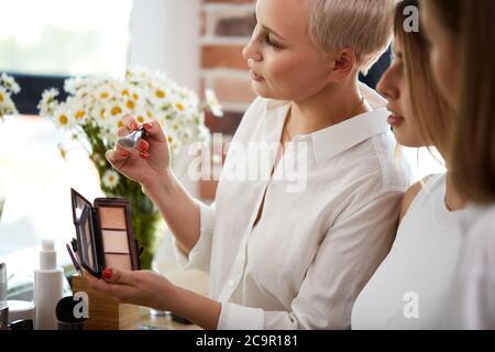 Junge kaukasische professionelle Lehrer visagiste Ausbildung ihrer Schüler Make-up-Künstler in der Meisterklasse in Schönheitssalon zu werden - Stockfoto