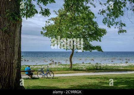 Ein unverkennbarer Mann mit Fahrrad macht eine Pause am Wasser in Visby auf Gotland. Gotland ist die größte schwedische Insel in der Ostsee. - Stockfoto