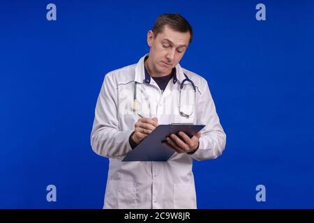 Männlicher Arzt in einem weißen Mantel posiert auf einem blauen Hintergrund Stockfoto