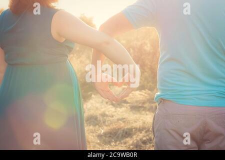 Schwangere Frau und ihr Mann schauen auf den Sonnenuntergang und halten ihre Hände in Herzform. Nahaufnahme. Familie, Schwangerschaft, Liebeskonzept, Hintergrund, Wand