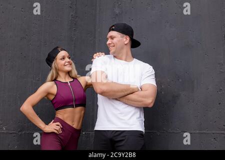 Schöne junge paar Bodybuilder in hellen Sportswear posiert auf grauem Hintergrund im Freien - Stockfoto