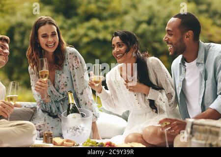 Junge Leute, die Champagner beim Picknick trinken. Freunde hängen an einem Wochenende im Park. - Stockfoto