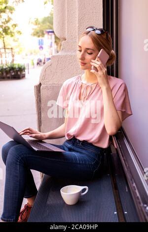 Porträtaufnahme einer jungen Frau, die einen Anruf hat und einen Laptop benutzt, während sie im Café sitzt.