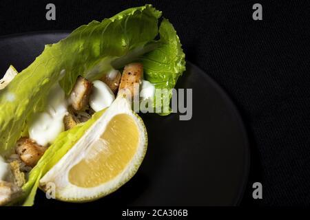 Hausgemachter Caesar-Salat mit Huhn, Salat, Zitrone, Toast, caesar-Sauce, Käse und Knoblauch. Auf dunklem Hintergrund. Gesunde Ernährung Konzept.