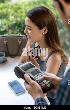 Asiatische Frau Kunden halten kontaktlose Kreditkarte für die Online-Zahlung nach dem Essen in neuen normalen sozialen Abstand Restaurant. Online - Stockfoto