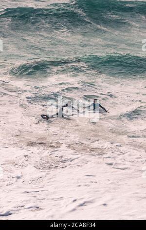 Teenager, die sich in den wilden Meeren vor der Küste von Newquay in Cornwall Vergnügen. - Stockfoto