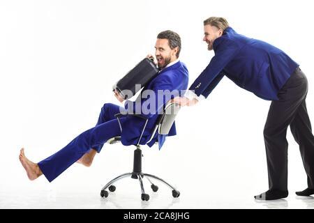 Mann in Anzug oder Geschäftsmann schieben Bürostuhl mit Kollegen auf, isoliert auf weißem Hintergrund. Geschäftsleute mit lächelnden Gesichtern haben Spaß im Büro. Entertainment-Konzept im Büro. - Stockfoto